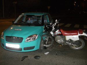 Teal-sedan-with-motorcycle-crashed-on-side