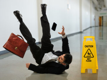man-in-suit-slips-on-smooth-wet-floor-caution-sign